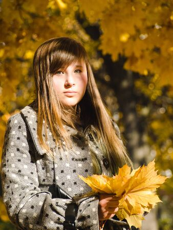 A teenage girl with a bouquet of autumn leaves