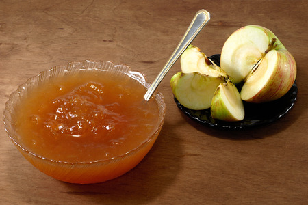 Apple jam on a rustic wooden background