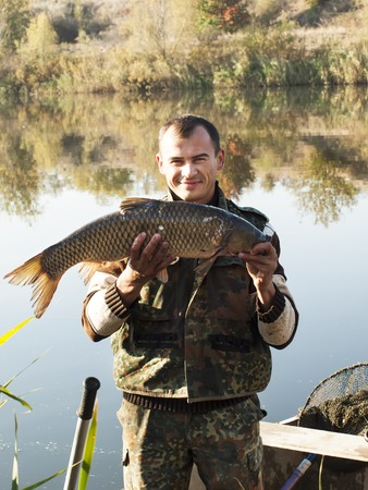 Fisherman With fish Mirror Carp. Fishing on river on autumn