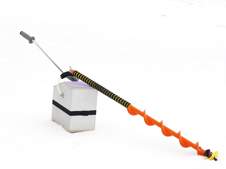 Small hand operated ice auger used in ice fishing on a background of snow and ice. Stock Photo
