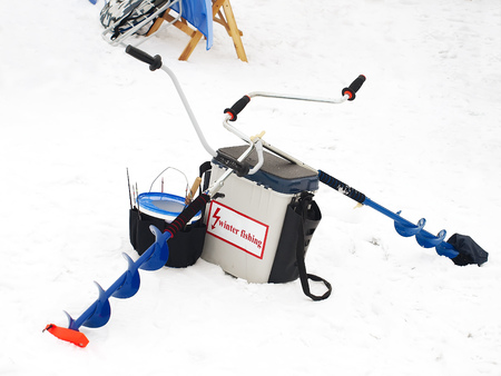 Winter fishing.Fishing rods and accessories on a background of snow and ice.