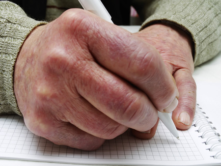 Closeup of the wrinkled hands of an old caucasian man holding pen and paper, wearing a green sweater 版權商用圖片 - 74260759