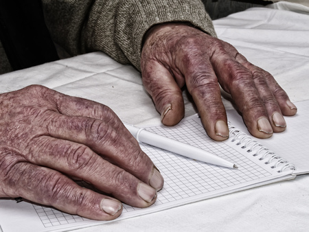 Closeup of the wrinkled hands of an old caucasian man holding pen and paper, wearing a green sweater