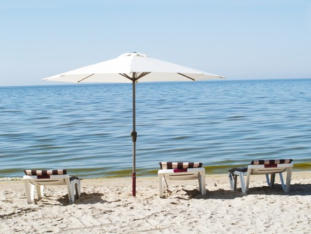 Three sun loungers and a beach umbrella on a deserted beach. The perfect concept of relaxation