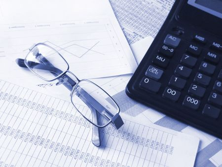 Glasses and calculator on financial documents. Toned blue. Shallow DOF. Stock Photo