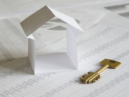 Paper house with key on financial documents. Shallow DOF. photo