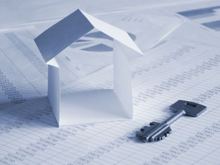 Paper house with key on financial documents. Toned blue. Shallow DOF. photo