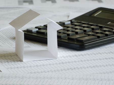 Paper house and calculator on financial documents. Shallow DOF. photo