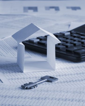 Paper house with key and calculator on financial documents. Toned blue. Shallow DOF. photo