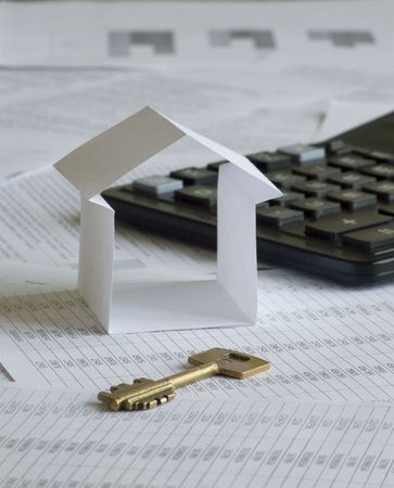 Paper house with key and calculator on financial documents. Shallow DOF. photo