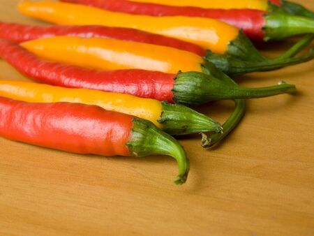 indian cookery: Row of the red and yellow chili peppers. Shallow DOF. Stock Photo