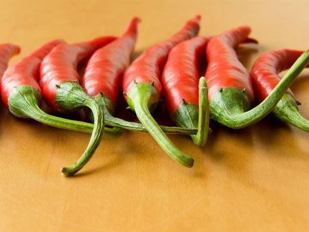 Row of the red hot chili peppers. Shallow DOF. Stock Photo - 5384405