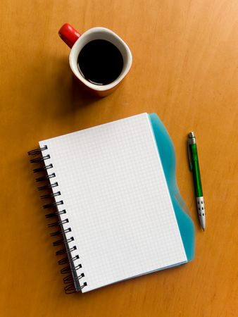 Coffee cup, spiral squared notebook and pen on the wooden table. Viewed from above.