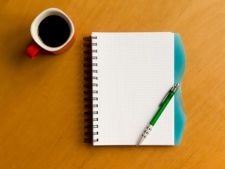 Coffee cup, spiral notebook and pen on the wooden table. Viewed from above. photo