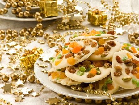 Homemade white chocolate cookies decorated with dried apricots, pistachios, raisin, candied fruits and walnuts. Shallow dof. photo