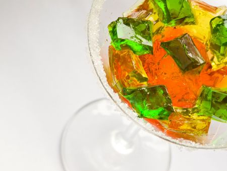 Glass with fruit jelly cubes, isolated over white. Shallow dof. photo