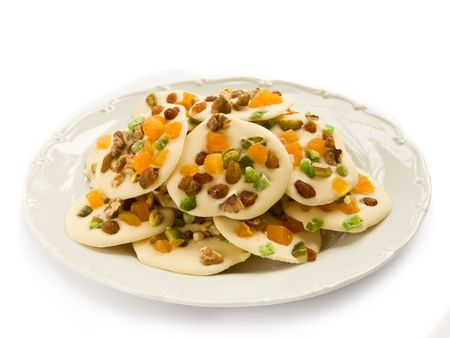 Homemade white chocolate cookies decorated with dried apricots, pistachios, raisin, candied fruits and walnuts, isolated over white.  photo