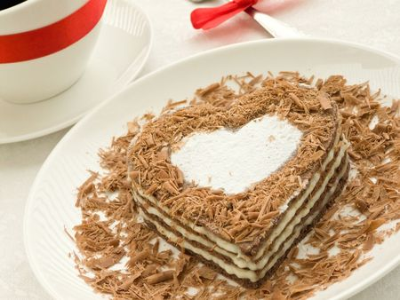 Plate with sweet chocolate heart-shaped cake and coffee cup. Shallow dof. photo