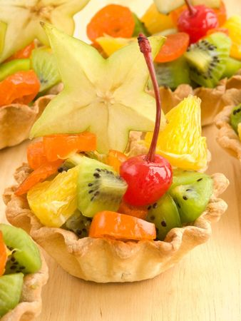 Group of fruit tartlets on wooden background. Shallow dof. photo