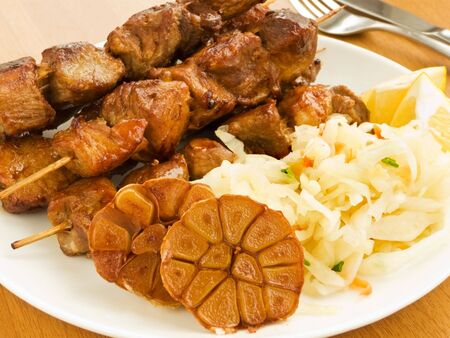 Plate with grilled pork kebabs and different kinds of vegetables garnish. Shallow dof. photo