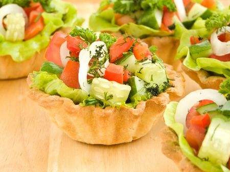 Group of the vegetable tartlets on wooden background. Shallow dof.