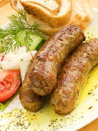 chorizos asados: Plato con salchichas a la parrilla, verduras y pan. Kelvin superficial.
