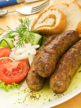 Dinner plate with grilled sausages, vegetables and bread. Shallow dof. Stock Photo - 6731971