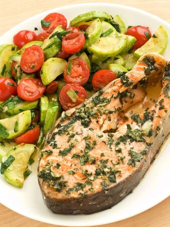 Plate with baked salmon steak and warm vegetable salad. Shallow dof. photo