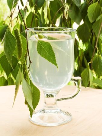 Glass with fresh birch sap. Shallow dof.