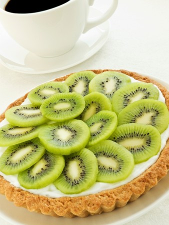 Plate with homemade kiwi tart and coffee cup. Shallow dof. photo