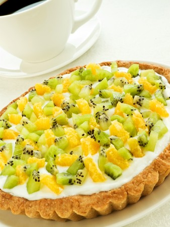 Plate with homemade orange-kiwi tart and coffee cup. Shallow dof. photo