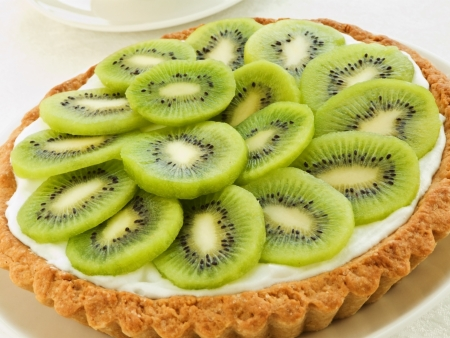 fresh baked: Plate with homemade kiwi tart and coffee cup. Shallow dof.