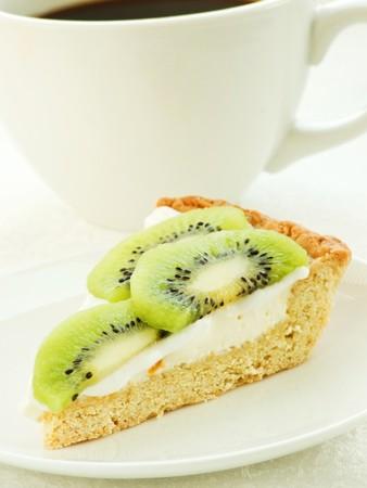 Coffee cup and slice of kiwi tart. Shallow dof. photo