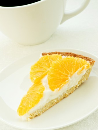 orange tart: Coffee cup and slice of orange tart. Shallow dof.