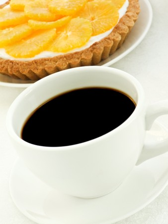orange tart: Plate with homemade orange tart and coffee cup. Shallow dof.
