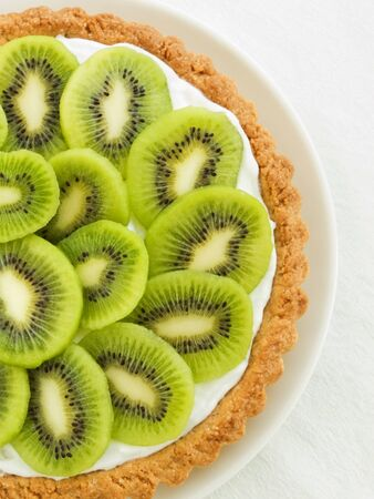 cheese cake: Plate with homemade kiwi tart, viewed from above.