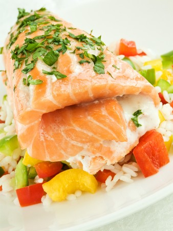 Plate with baked salmon and rice with vegetables. Shallow dof. Stock Photo