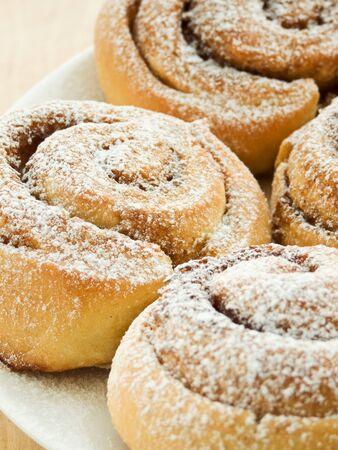 Sweet buns with cinnamon and powdered sugar. Shallow dof. photo