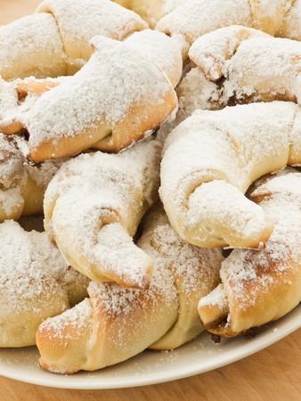 Homemade croissants with cinnamon and powdered sugar. Shallow dof. photo