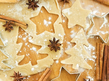 Christmas baking background: dough, cookie cutters and spices. Viewed from above.