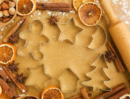 cookie cutters: Christmas baking background: dough, cookie cutters, spices and nuts. Viewed from above.
