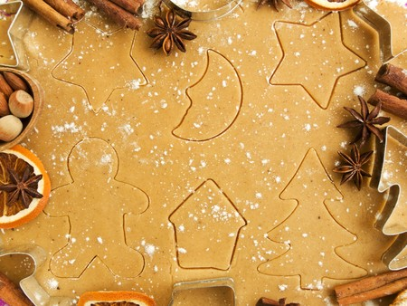 Christmas baking background: dough, cookie cutters, spices and nuts. Viewed from above. photo