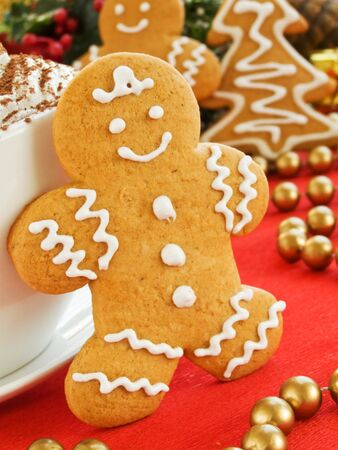 Homemade gingerbread man cookie and cup of chocolate with whipped cream. Shallow dof. photo