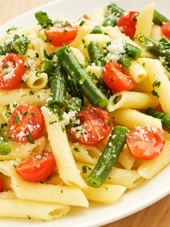penne: Italian pasta penne with cherry tomatoes and green beans. Shallow dof.