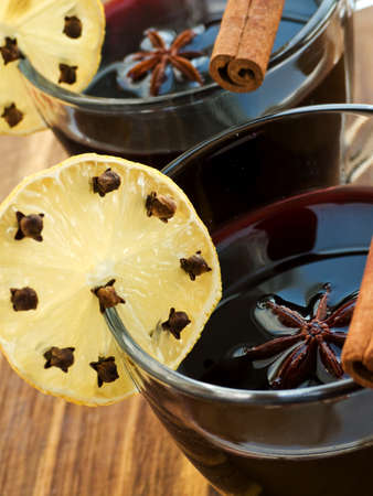 Mulled wine with slice of lemon and spices. Shallow dof. photo