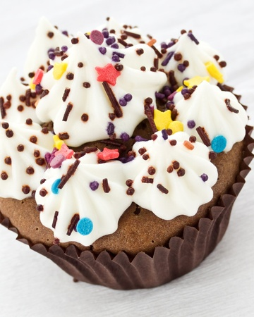 Chocolate cupcake with whipped cream and icing. Shallow dof. photo