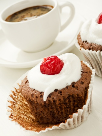 Chocolate cupcake with and coffee cup. Shallow dof. Stock Photo