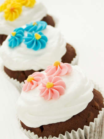 Chocolate cupcakes with whipped cream and icing. Shallow dof. photo