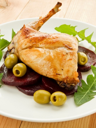 Plate with roasted rabbit leg and vegetable garnish. Shallow dof. photo