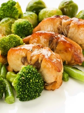 Plate with roasted rabbit steaks and vegetable garnish. Shallow dof. photo